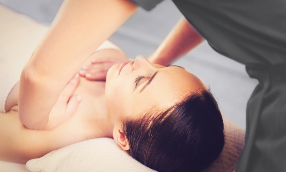 Serene girl is enjoying massage at spa. Masseuse is standing and pampering her breast