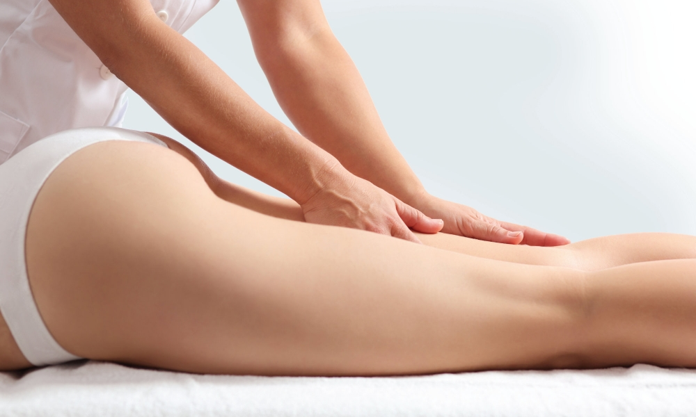 Side view of a woman legs receiving a massage therapy isolated on a white background